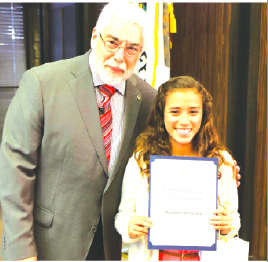 """La Mirada Mayor Steve De Ruse presents 7th grade student Madeline Hernandez of St. Paul of the Cross with a certificate of recognition for winning 1st Place in her age group for the annual """"Love a Tree"""" Poster Contest."""
