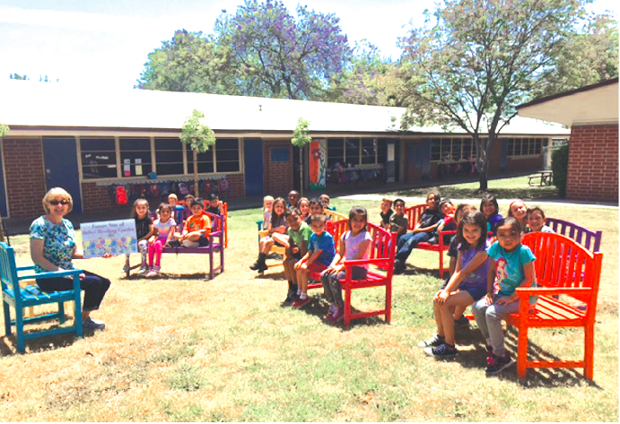 A Dulles Elementary School classroom takes its reading outside to a brand new outdoor reading space. Dulles Elementary and Love La Mirada partnered to build eight benches, a chair and table, and planted three trees to create the reading space.